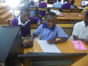 Derrick (left) at a computer lesson conducted by Fundi Bots
